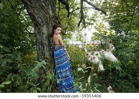 Portrait of a beautiful young woman wearing blue dress in the forest
