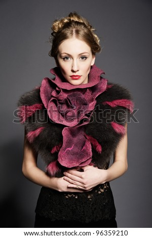 Portrait of a beautiful young woman wearing fur coat. Over gray background.