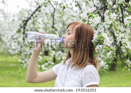Portrait of a beautiful young woman who drinks water in park among blossoming trees - stock photo