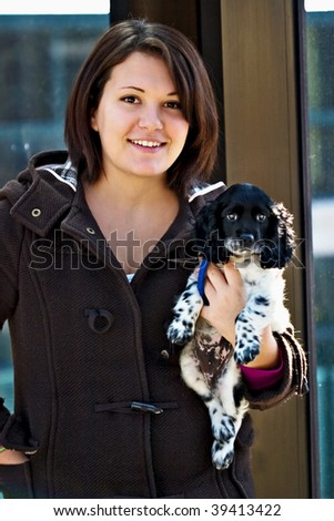 Portrait of a beautiful young woman with a Cocker Spaniel puppy. - stock photo