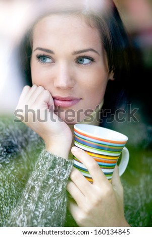 Portrait of a beautiful young woman with a cup of tea coffee looking out the window in the winter. Shallow depth of field. - stock photo