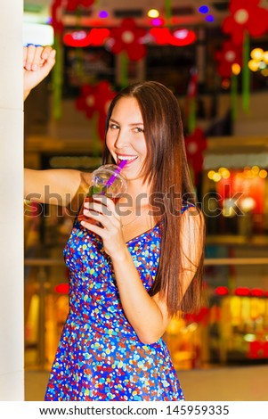Portrait of a beautiful young woman with a glass of juice in shopping center  - stock photo