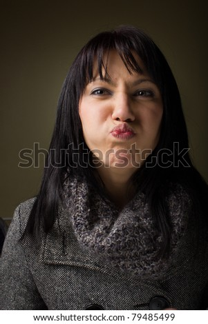 Portrait of a beautiful young woman with a jacket with a silly facial expression. - stock photo