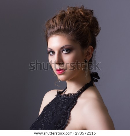 Portrait of a beautiful young woman with a magnificent high hairstyle and bright makeup.