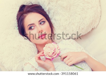 portrait of a beautiful young woman with a pink rose lying on the sofa - stock photo