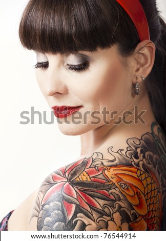 Portrait of a beautiful young woman with a tattoo on the backs - stock photo