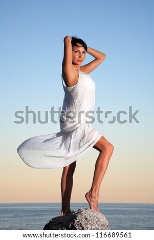 portrait of a beautiful young woman with a white dress posing on  a stone close to the sea - stock photo