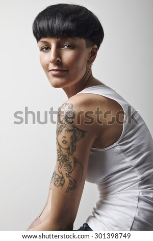 Portrait of a beautiful young woman with black mushroom hair cut and lot of tattoos on her body. Looking at camera.  - stock photo