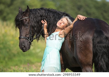 Portrait of a beautiful young woman with black stallion. - stock photo