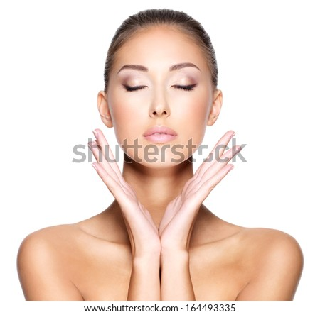 Portrait of a beautiful young woman with clear healthy skin that wants to touch her face with both hands - stock photo