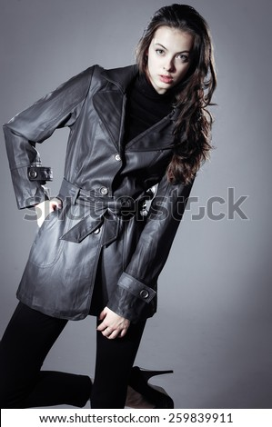 Portrait of a beautiful young woman with coat in studio - stock photo