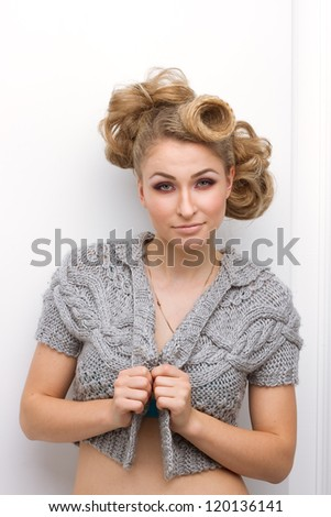 portrait of a beautiful young woman with curly blond hair and glamour make-up wearing a gray knit sweater