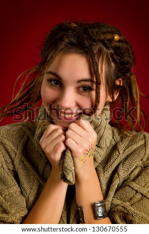 portrait of a beautiful young woman with dreadlocks on a red background