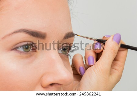 Portrait of a beautiful young woman with esthetician making makeup eye shadows. Stylist causes make up the beautiful model. Behind the scenes, making makeup - stock photo