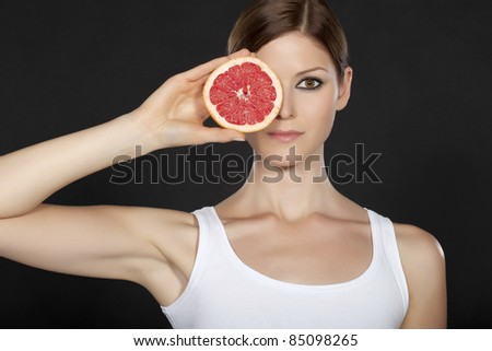 Portrait of a beautiful young woman with face partly covered by grapefruit