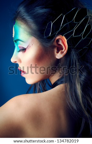 Portrait of a beautiful young woman with fantasy makeup. Dark background. - stock photo