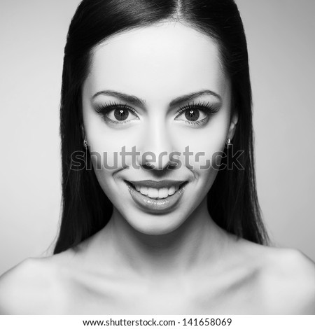 Portrait of a beautiful young woman with great white shiny smile posing over light-gray background. Healthy skin. Black and white (monochrome) studio shot