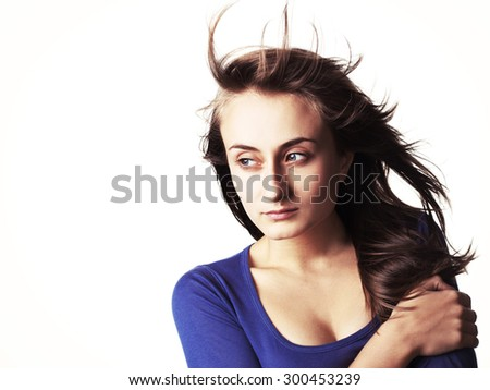 Portrait of a beautiful young woman with hair flying isolated on white with copy-space. High-contrast image with intentional color shift