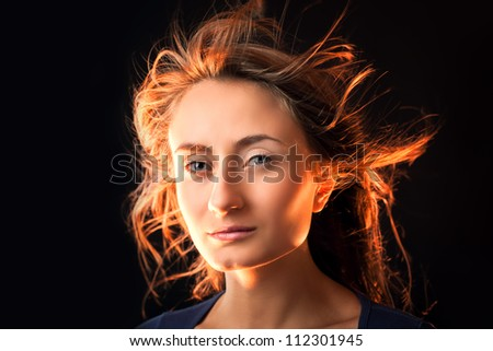 Portrait of a beautiful young woman with hair flying on dark background - stock photo