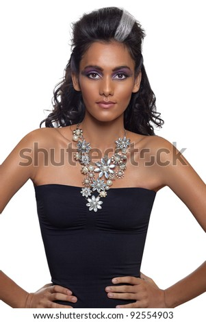 portrait of a beautiful young woman with long curly hair and tanned skin wearing an expensive necklace and black dress. - stock photo