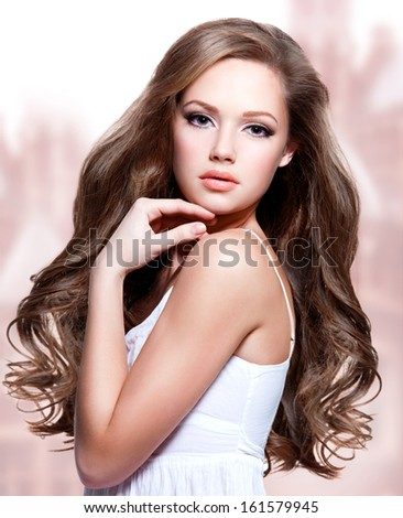 Portrait of a beautiful young woman with  long curly hairs - stock photo