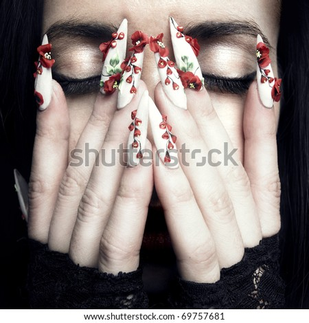 Portrait of a beautiful young woman with long designer nails - stock photo
