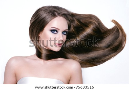 Portrait of a beautiful young woman with long hair and bright black eye make-up- horizontal - stock photo