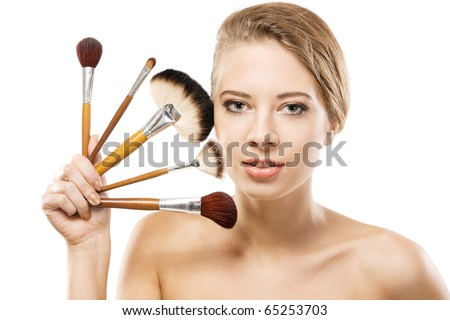Portrait of a beautiful young woman with makeup brushes