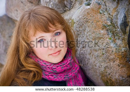 portrait of a beautiful young woman with pink scarf, she is standing near a wall made of stones
