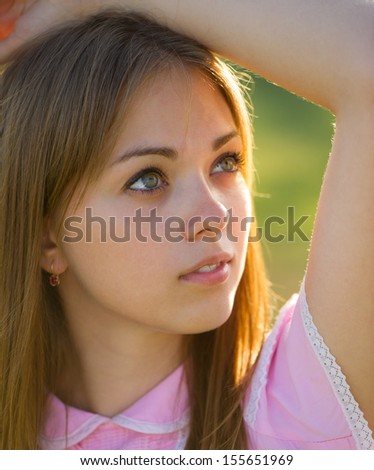 portrait of a beautiful young woman with raised hand on a sunny day