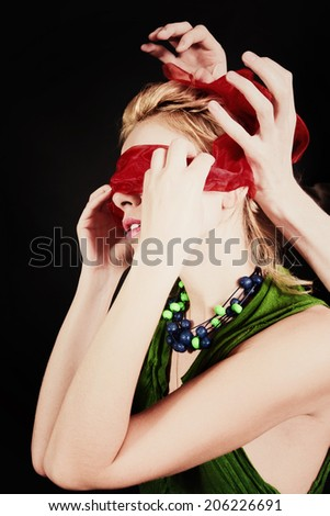 Portrait of a beautiful young woman with red blindfold closeup - stock photo