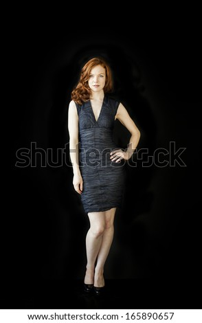 Portrait of a beautiful young woman with red hair and blue eyes shot on black background.