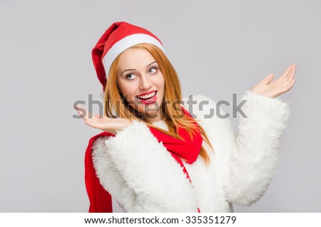 Portrait of a beautiful young woman with red Santa hat looking to the side smiling with hands up. Happy girl dressed for Christmas time. Merry Christmas. - stock photo