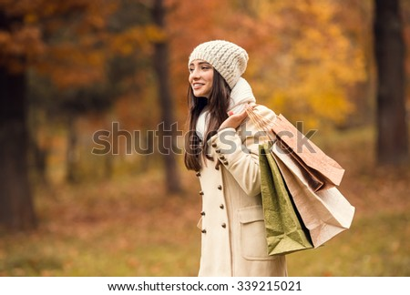 Portrait of a beautiful young woman with shopping bags for shopping while walking in the autumn park - stock photo