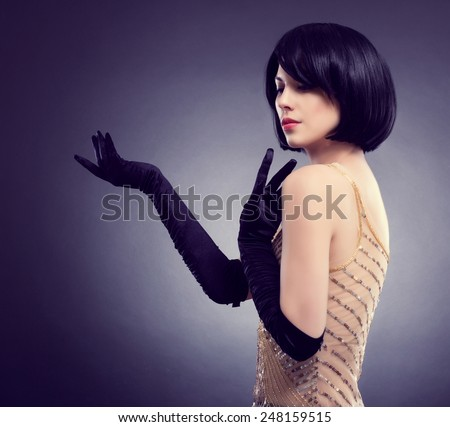 Portrait of a beautiful young woman with stylish hairstyle and black gloves. Fashion Image. - stock photo