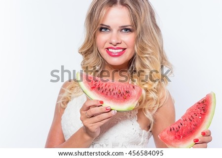 Portrait of a beautiful young woman with watermelon on a white background. Happy girl eating watermelon. Summer.