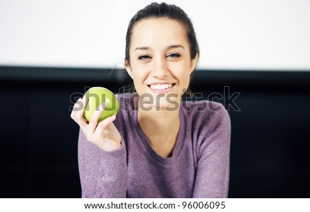 portrait of a beautiful young woman wiyh green apple - stock photo