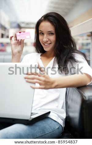 Portrait of a beautiful young woman working on laptop while sitting at cafe or shopping mall
