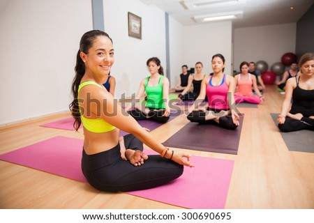 Portrait of a beautiful young yoga instructor smiling during one of her classes - stock photo