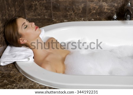 Portrait of a beauty young adult attractive sexy and sensuality pretty brunette woman in bath relaxing. Close up of young woman in bathtub bathing - stock photo