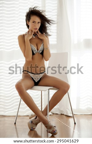 Portrait of a beauty young adult slim sexy and sensuality attractive pretty brunette woman in black erotic lingerie against the sunlight window - stock photo