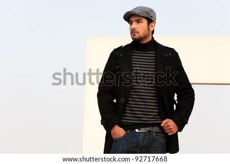 Portrait of a biracial man wearing over coat, portrait of a handsome and confident young man wearing a muffler and over coat with a cap - stock photo