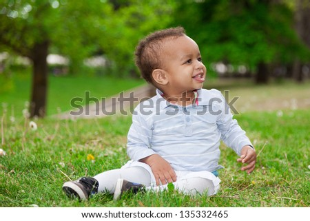 Portrait of a black african american baby boy playing  in the park - African children - stock photo