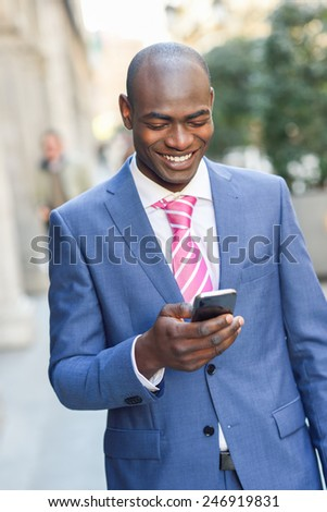 Portrait of a black businessman wearing suit reading his smart phone in urban background - stock photo