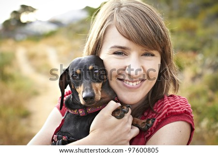 Portrait of a black Dachshund dog and young lady on sand path - stock photo