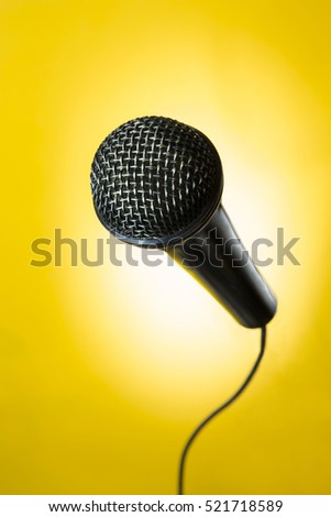 portrait of a black microphone in yellow background / black microphone in yellow background