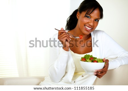 Portrait of a black young woman looking at you as she eats her green salad at home indoor. With copyspace. - stock photo