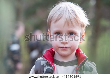 Portrait of a blond boy in the military vest walking on the street.