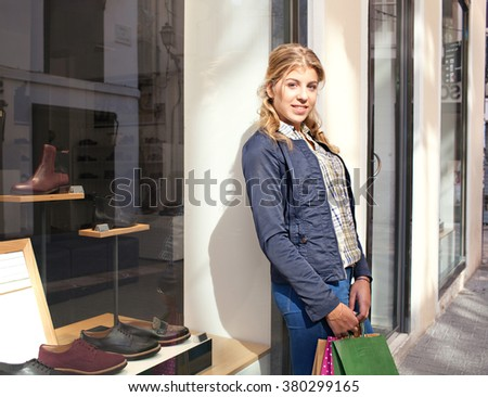 Portrait of a blond caucasian teenager girl relaxing in a shopping street by shoe store window, looking at camera smiling, outdoors. Adolescent consumer lifestyle. Young woman with shopping bags. - stock photo