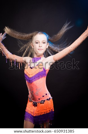 Portrait of a blond girl in orange and purple dance costume for stage performance